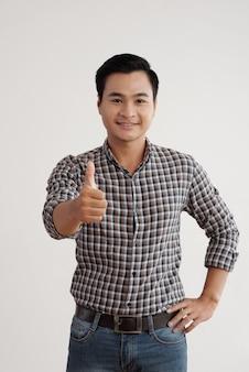 Vrolijke aziatische mens in plaidoverhemd en jeans die zich in studio met zijn omhoog duim bevinden