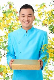 Vrolijke aziatische mens in traditioneel turkoois jasje die zich tegen bloeiende mimosa bevinden en doos houden