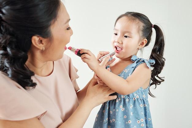 Vrolijke aziatische moeder en dochter die lippenstift op de lippen van elkaar toepassen wanneer ze zich 's ochtends klaarmaken