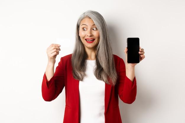 Vrolijke aziatische rijpe vrouw die het lege smartphonescherm en creditcard, concept elektronische handel toont.