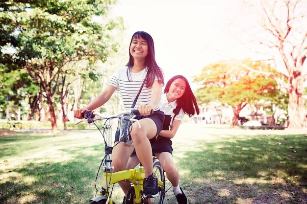 Vrolijke aziatische tiener berijdende fiets in pulbic park
