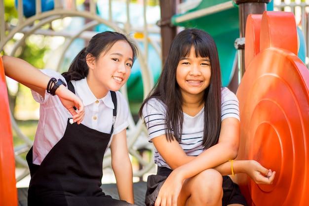 Vrolijke aziatische tiener die in kinderenspeelplaats lachen