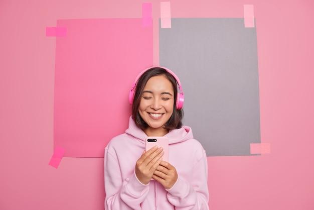 Vrolijke aziatische tienermeisje gebruikt mobiele telefoon applicatie voor het luisteren van muziek draagt stereo koptelefoon op oren geniet van ontspannend lied na het studeren.