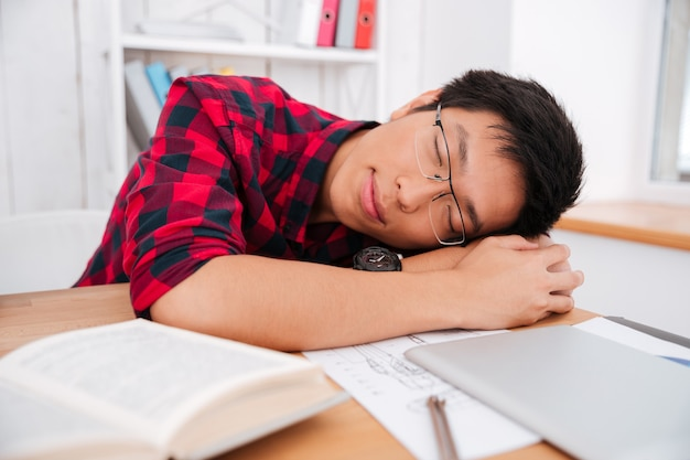 Vrolijke aziatische tienerstudent met een bril die in de klas slaapt op tafel in de buurt van notitieboekje en boeken