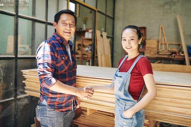 Vrolijke aziatische timmerman en klant handen schudden na bespreking van project