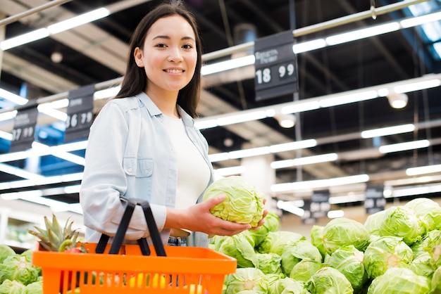 Vrolijke aziatische vrouw die kool in markt kiezen