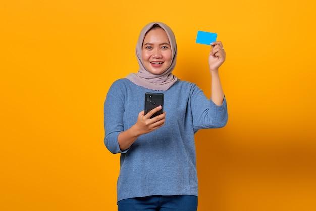 Vrolijke aziatische vrouw die mobiele telefoon vasthoudt en creditcard toont over gele achtergrond