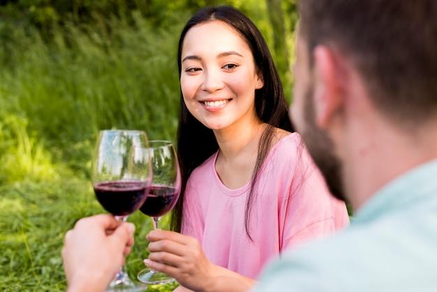 Vrolijke aziatische vrouw die wijnglazen met vriend en het glimlachen roosteren