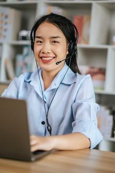 Vrolijke aziatische vrouw draagt een headset die lacht en gebruikt een laptop videogesprek streamconferentie om online te werken terwijl ze tijdens quarantaine covid-19 zelfisolatie thuis werken vanuit huis concept