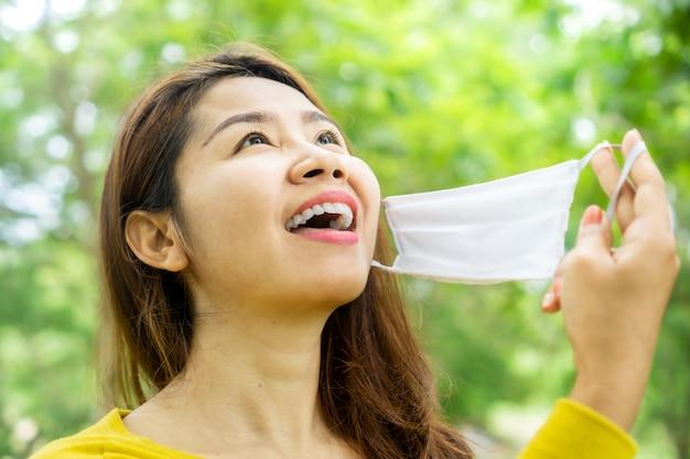 Vrolijke aziatische vrouw hand opstijgen gezichtsmasker nadat de quarantaine voorbij is