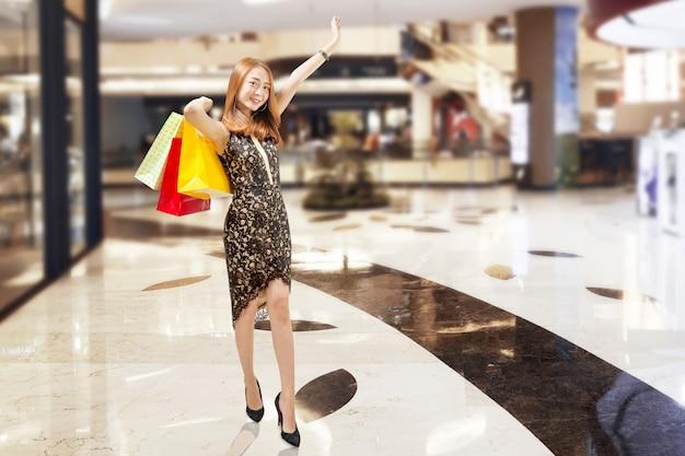 Vrolijke aziatische vrouw in zwarte jurk met boodschappentassen