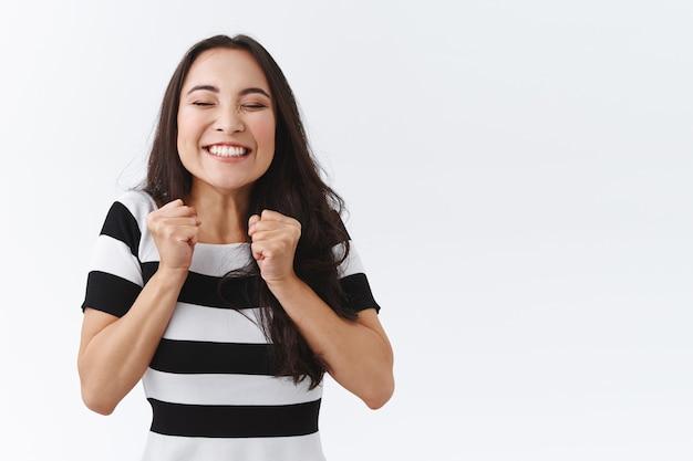 Vrolijke aziatische vrouw kan niet wachten om vakantie halloween te vieren, vreugdevol en opgewonden te dansen, vuisten in de buurt van borst dicht te knijpen en breed te glimlachen, triomfantelijk, opgewonden witte achtergrond te staan