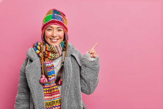 Vrolijke aziatische vrouw kleedt zich voor koud winterweer geeft aan dat op lege ruimte iets geweldigs laat zien draagt gebreide muts bontjas en sjaal om nek geïsoleerd over roze muur