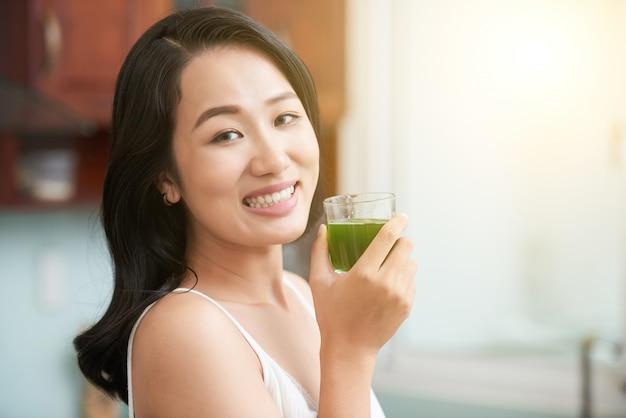 Vrolijke aziatische vrouw met glas groen sap