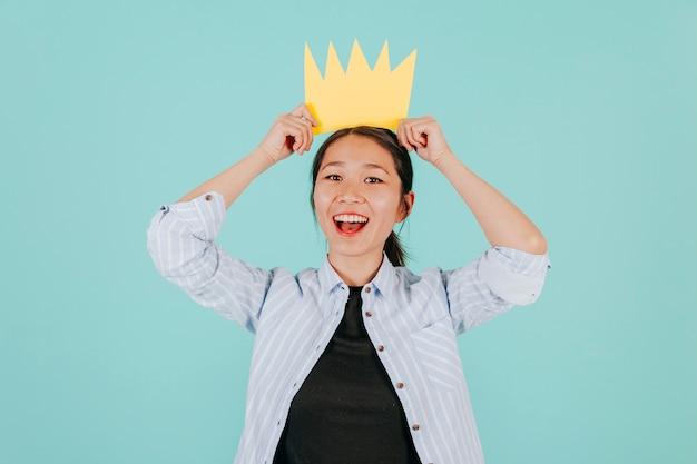 Vrolijke aziatische vrouw met papieren kroon