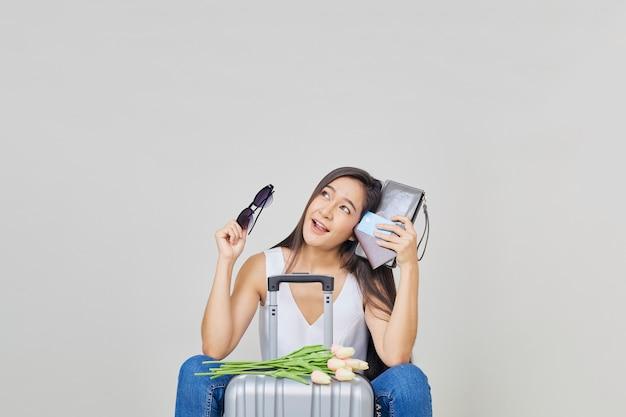 Vrolijke aziatische vrouw met reiskoffer