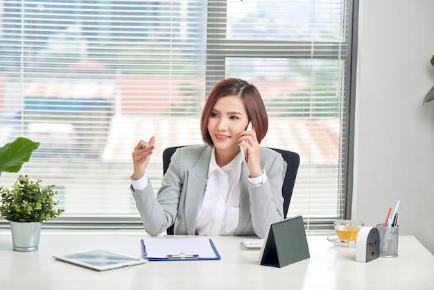 Vrolijke aziatische vrouw praten op mobiele telefoon zittend op een bureau met laptop. zakenvrouw in casuals telefoneren en lachen.