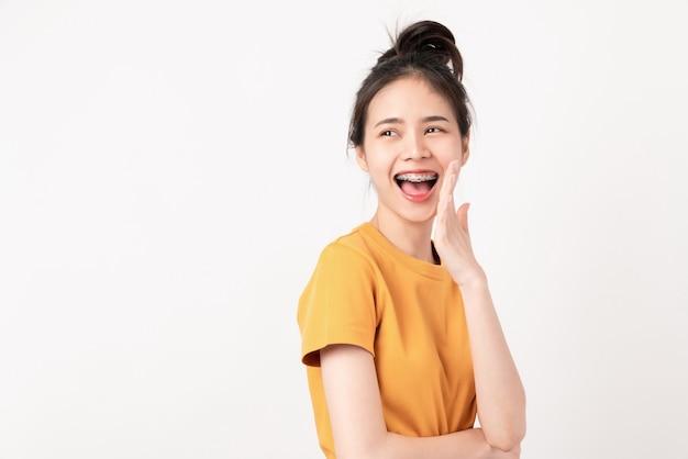 Vrolijke aziatische vrouw staande en aankondigend met handen aan de mond en een geheim te vertellen in het dragen van een geel shirt