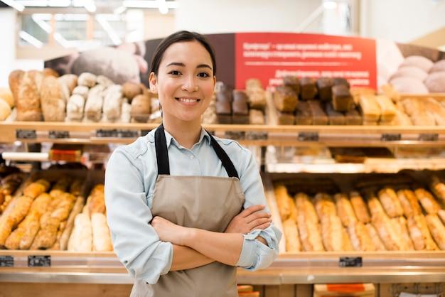 Vrolijke aziatische vrouwelijke bakkerijverkoper met wapens die in supermarkt worden gekruist