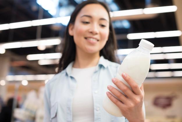 Vrolijke aziatische vrouwelijke holdingsfles melk bij supermarkt