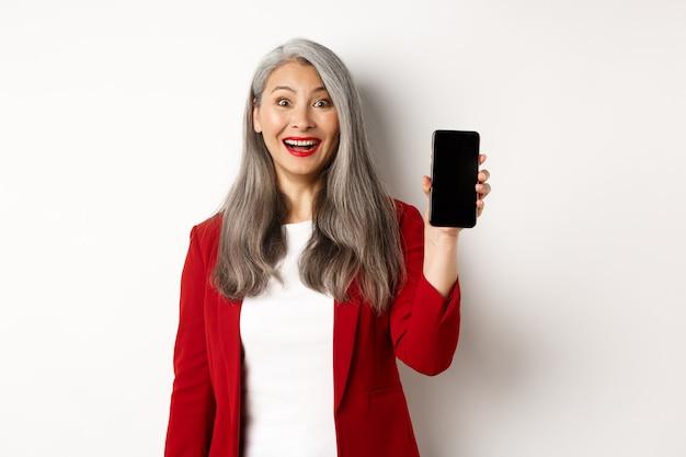 Vrolijke aziatische vrouwelijke ondernemer met gsm-scherm, lachend geamuseerd, staande op een witte achtergrond.