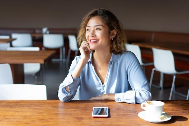 Vrolijke aziatische vrouwelijke ondernemer zittend aan tafel in café