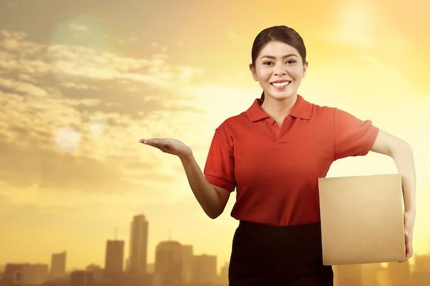 Vrolijke aziatische vrouwenkoerier met pakket en het tonen van iets