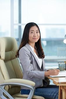 Vrolijke aziatische vrouwenzitting bij bureau in bureau, die en voor camera schrijven stellen