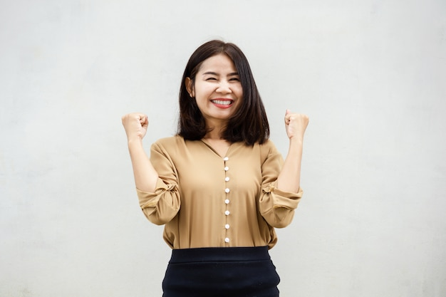Vrolijke aziatische zaken vrouw die lacht tegen grijze muur