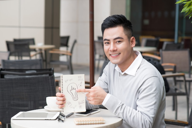 Vrolijke aziatische zakenman die creatieve ideedocumenten toont
