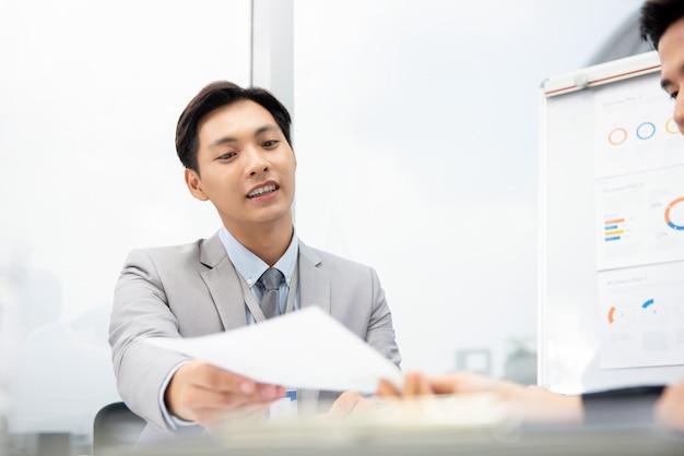 Vrolijke aziatische zakenman die het document van het businessplan voorstellen aan cliënt