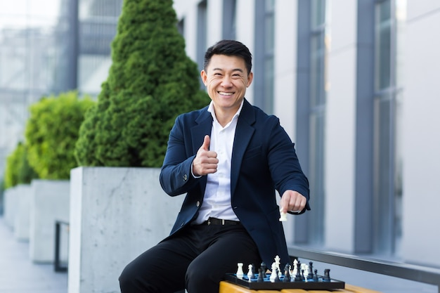Vrolijke aziatische zakenman die schaak speelt in de tuin, glimlachend en uitkijkend naar de camera