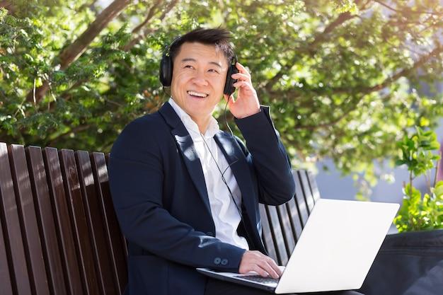 Vrolijke aziatische zakenman zittend op een bankje in een stadspark in het centrum en luisteren naar muziek op koptelefoon met behulp van een laptop. een man in een pak geniet van het buitenleven. ontspan en rust. levensstijl