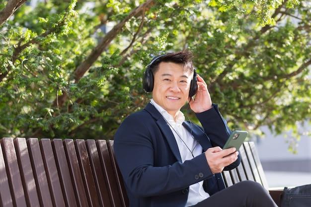 Vrolijke aziatische zakenman zittend op een bankje in een stadspark in het centrum en luisteren naar muziek op koptelefoon met telefoon in zijn handen. man in een pak geniet van het buitenleven. ontspan en rust. levensstijl
