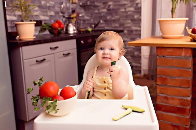 Vrolijke baby eet groenten, portret van een gelukkig meisje in een kinderstoel in de keuken