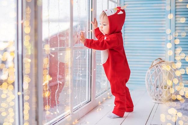 Vrolijke baby in het rendierkostuum van de rode kerstman speelt tegen de achtergrond van raam en lichten van slingers