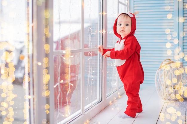 Vrolijke baby in het rendierkostuum van een rode kerstman speelt tegen de achtergrond van een raam en lichten van slingers