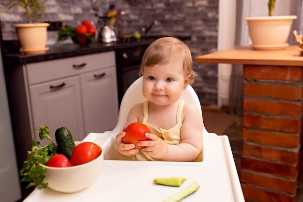 Vrolijke baby van 10-12 maanden eet groenten. portret van een gelukkig meisje in een kinderstoel in de keuken
