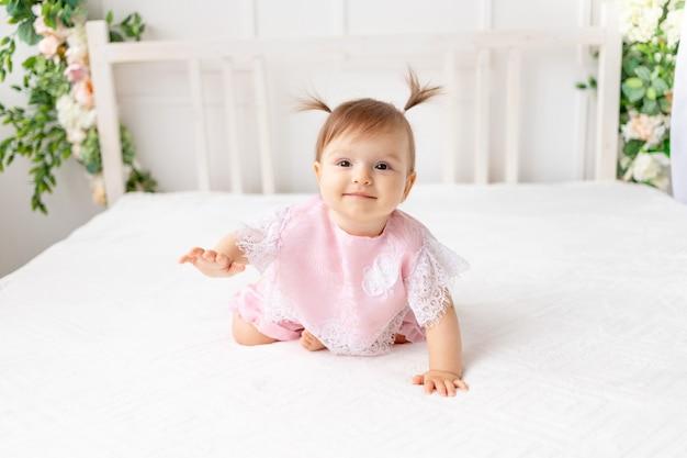 Vrolijke babymeisje zes maanden oud zittend in een heldere, mooie kamer op een wit bed in roze kleren en glimlachen