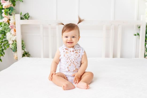 Vrolijke babymeisje, zittend in een heldere, mooie kamer op een wit bed in een kanten romper en glimlachen