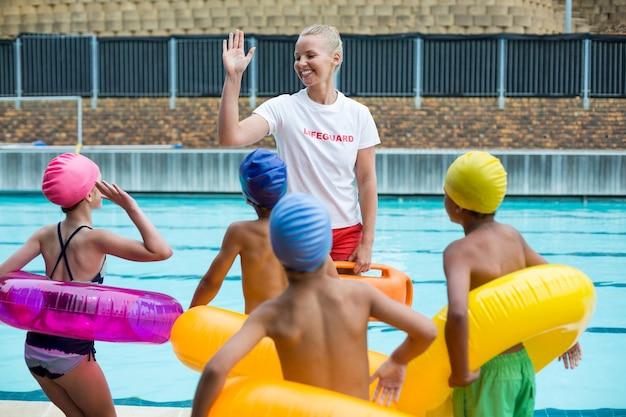 Vrolijke badmeester die kinderen instrueert bij het zwembad
