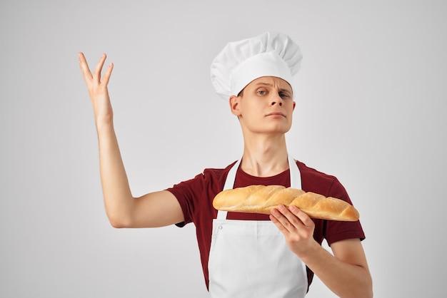 Vrolijke bakker met een brood in zijn handen die voedsel bakken bereidt