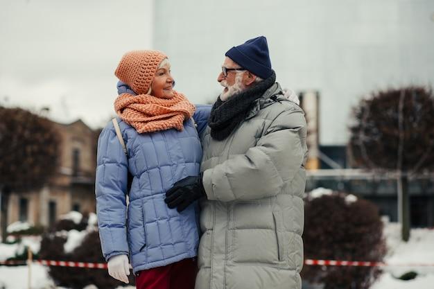 Vrolijke bebaarde gepensioneerde die naar zijn geliefde vrouw kijkt terwijl hij in de winter met haar op straat is