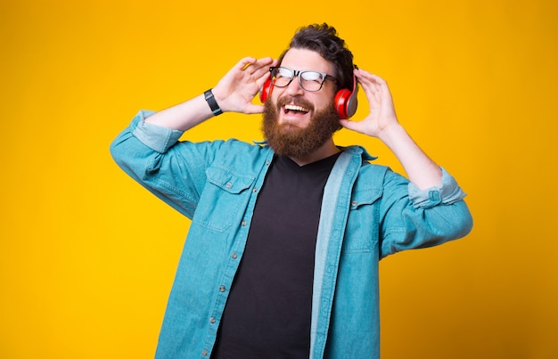 Vrolijke bebaarde hipster luistert naar de muziek via een koptelefoon op geel