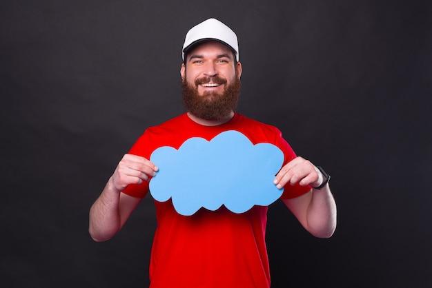 Vrolijke bebaarde hipster man in rood t-shirt met lege blauwe toespraak wolk