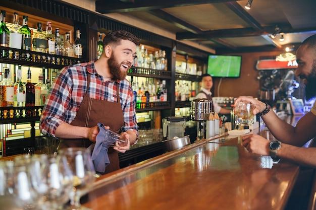Vrolijke, bebaarde jonge barman die lacht en praat met de klant in de bar