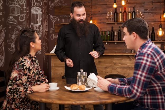 Vrolijke bebaarde jonge barman lachen en praten met klanten in restaurant. ontspannen stemming.