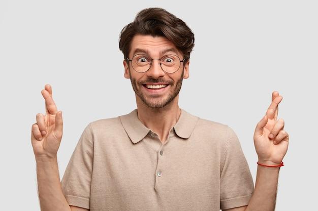 Vrolijke bebaarde jonge man met tevreden expressie, kruist vingers als hoop op geluk