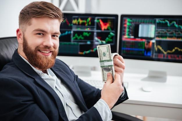 Vrolijke, bebaarde jonge zakenman die dollars op kantoor zit en vasthoudt