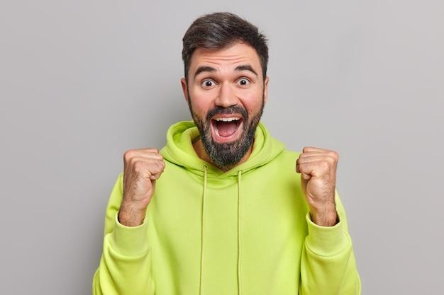 Vrolijke, bebaarde knappe man heft vuisten op in overwinningsgebaar viert succes